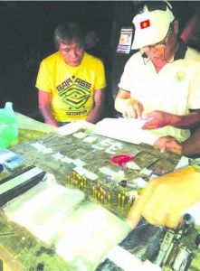 DRUG LORD. Eddie T. Vaño, (I) watches the inventory of shabu and firearms seized during his arrest in Carmen town yesterday afternoon.